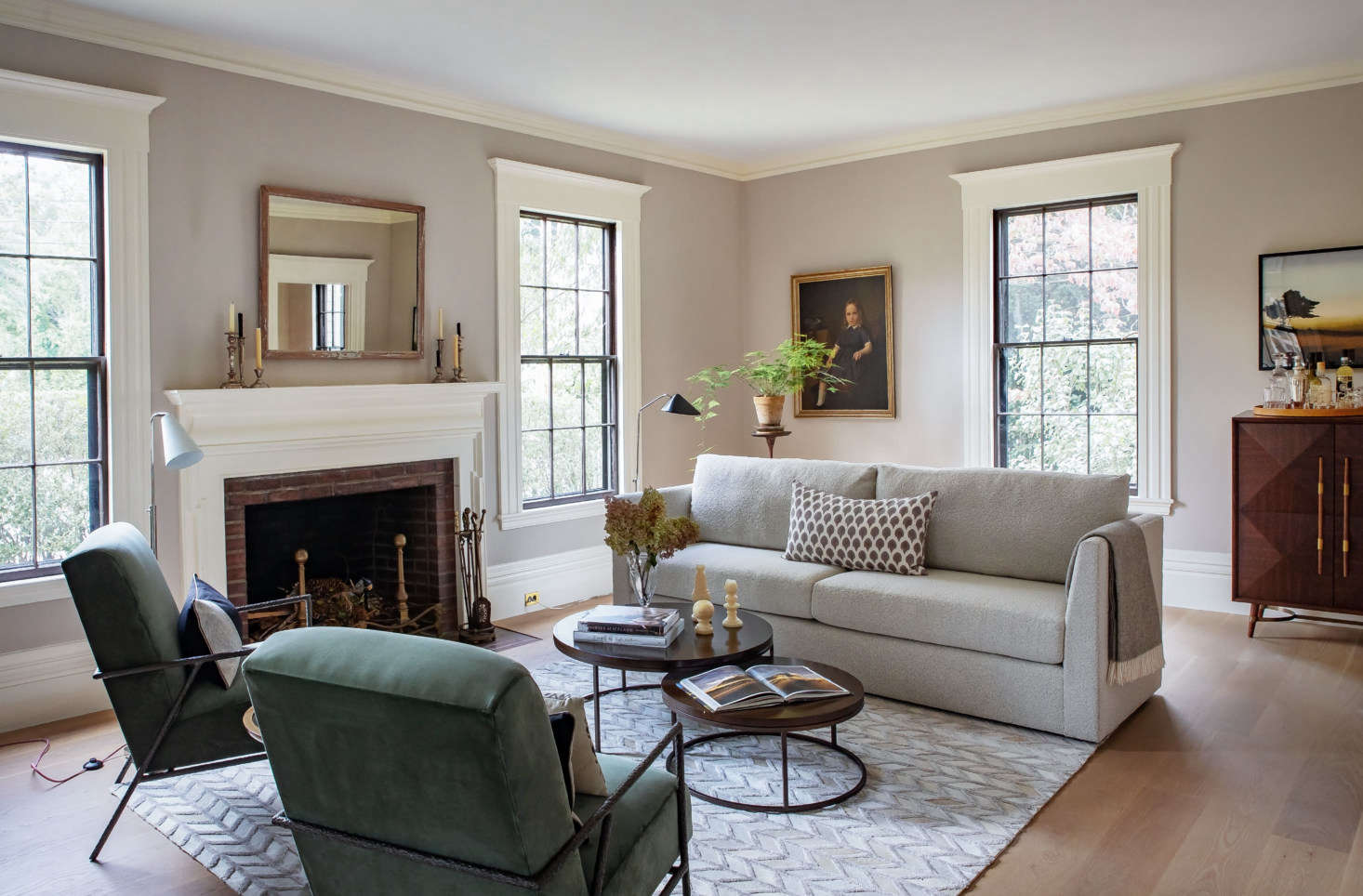 """The centerpiece of the room: Justine's oversized windows—and MG+BW's Franco II Studio Sofa. """"We've always believed home is, above all, a place of comfort,"""" says Allison O'Connor, president and CEO of MG+BW, """"and it's more important than ever now. The sofa, for instance, is where we've all been spending much more time, and we're committed to making ours incredibly comfortable in a sustainable manner."""" The Franco is inspired by 70s lounge furniture, with deep and relaxing seating and a soft boucle fabric. It's paired with the versatile Bassey Nesting Cocktail Table with chocolate-stained oak tops (and Justine's collection of vintage candlesticks on the mantel)."""
