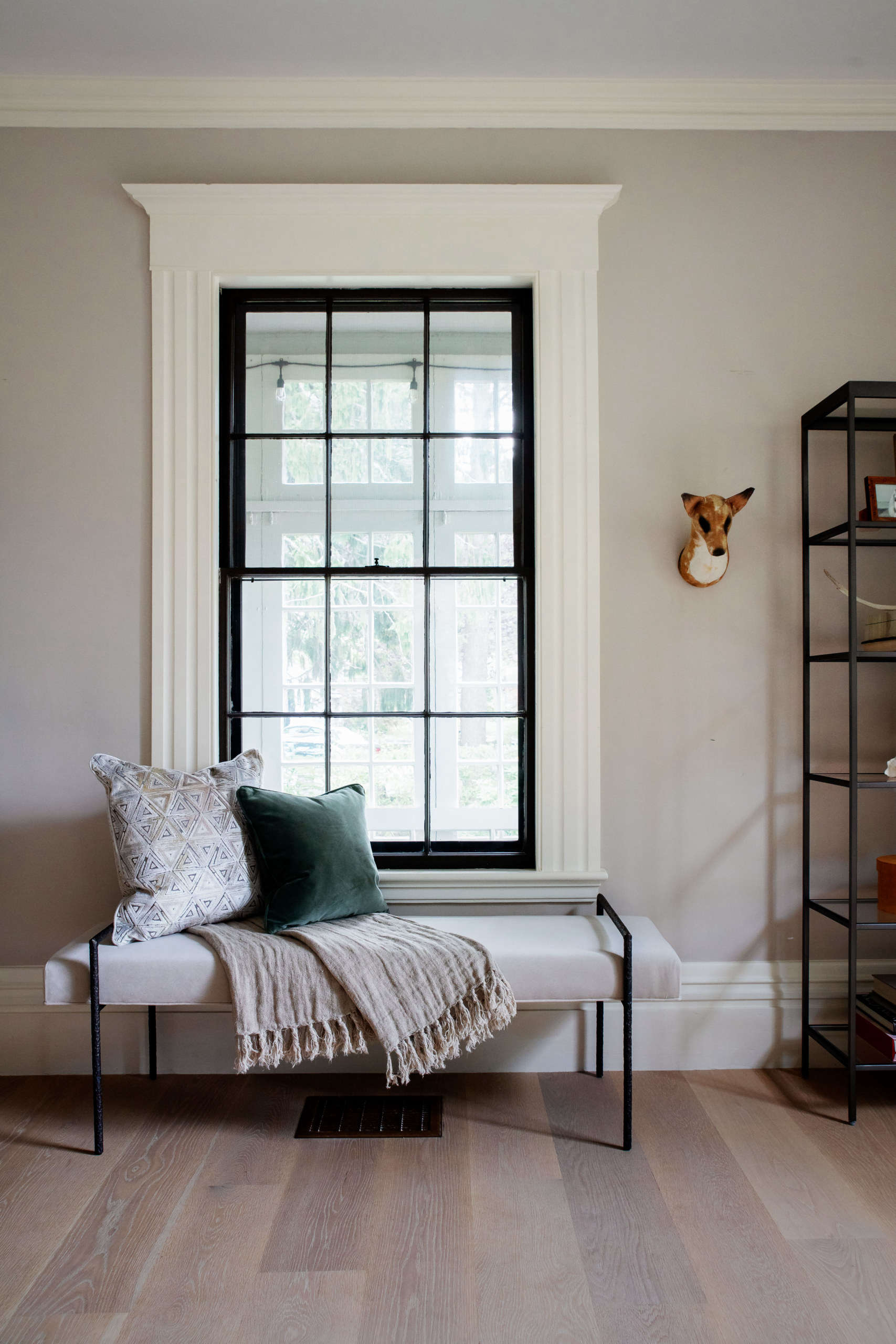 """The Yves Bench Ottoman—trimly sized to fit beneath a window, entryway, or at the end of a bed—makes for a cozy reading spot. It has a textured handmade frame finished in burnished bronze, and each piece is one of a kind. """"We want our collection to help people express their individuality and make their homes reflect them,"""" says Allison, and many pieces are customizable. """"For the Yves Bench, as with all our upholstery, you can choose from over 40 leathers and over 575 fabrics, including performance fabrics that are so easy to live with."""" On the wall is Justine's own fox bust by British textile artist Mister Finch (""""a prized possession,"""" she says)."""