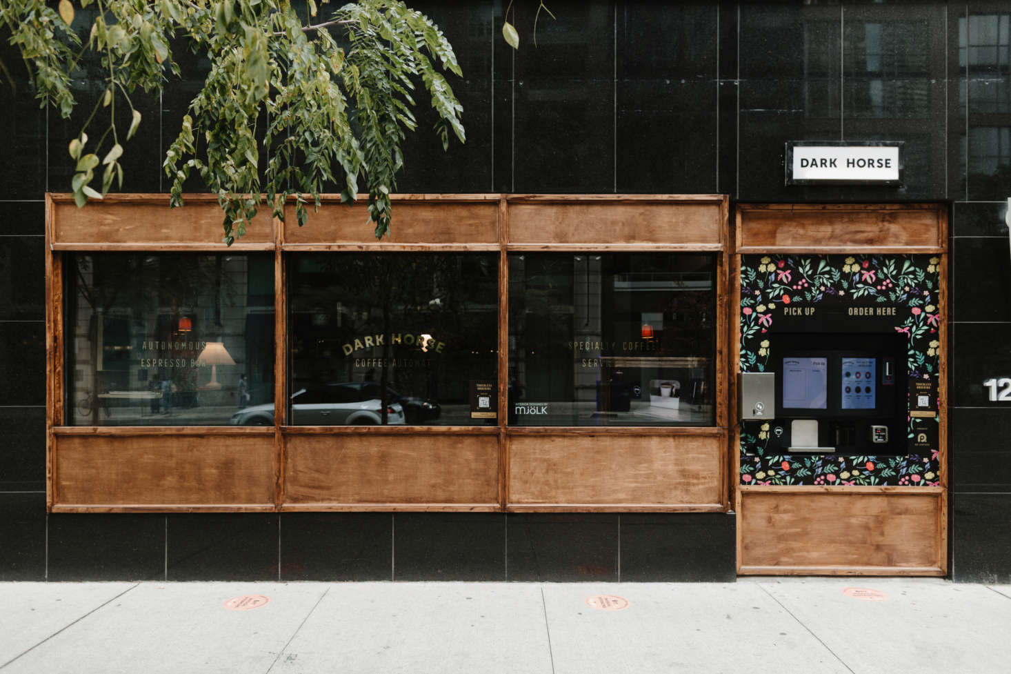 The facade features an outdoor ordering station; passersby can peer through the window at the stage-set-like coffee shop interior.