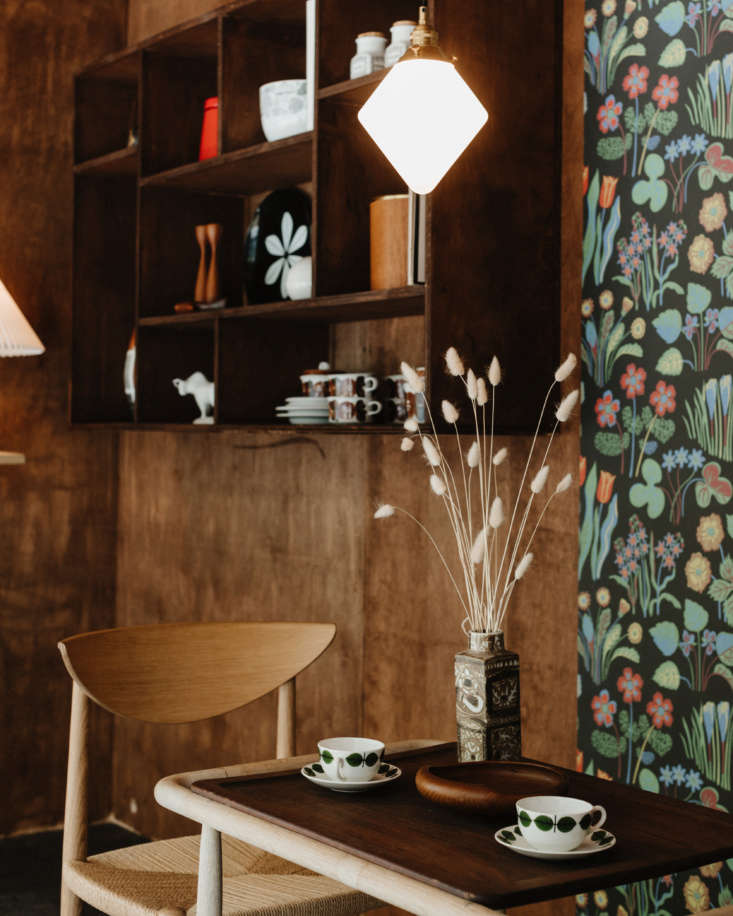 The table is set with vintage Bersa coffee cups by Stig Lindberg for Gustavsberg and a vintage Danish teak bowl. The Nils Thorsson Stoneware Vase is from Royal Copenhagen, and the Diamond Pendant Light hanging above was designed by Oji Masanori for Mjolk.