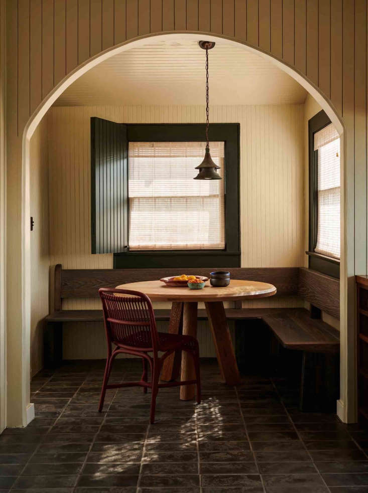 A perfectly appointed breakfast nook. Patrick designed the table, made from salvaged California coastal live oak, as well as the banquette. An antique copper lantern hangs above. The floors are locally made black terracotta tiles.