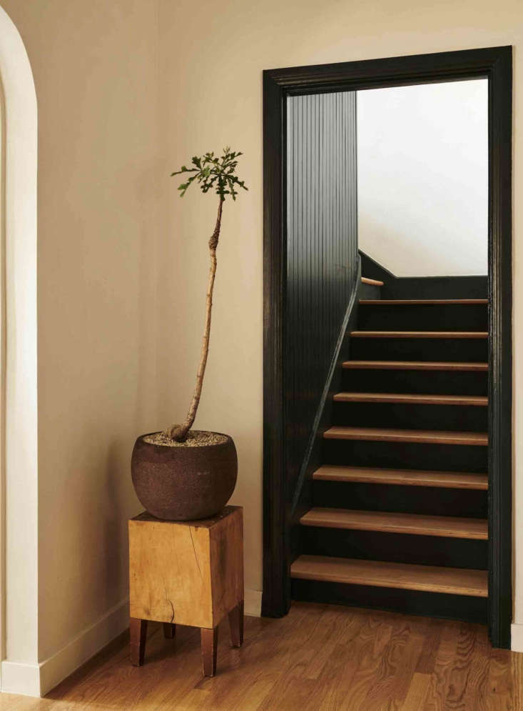 A small artful moment in an unexpected spot, thanks to a funky potted plant and the stool, an antique that once belonged to a now defunct Napa schoolhouse, it rests on. The oak stairs and some of the original oak flooring were salvaged and refinished.