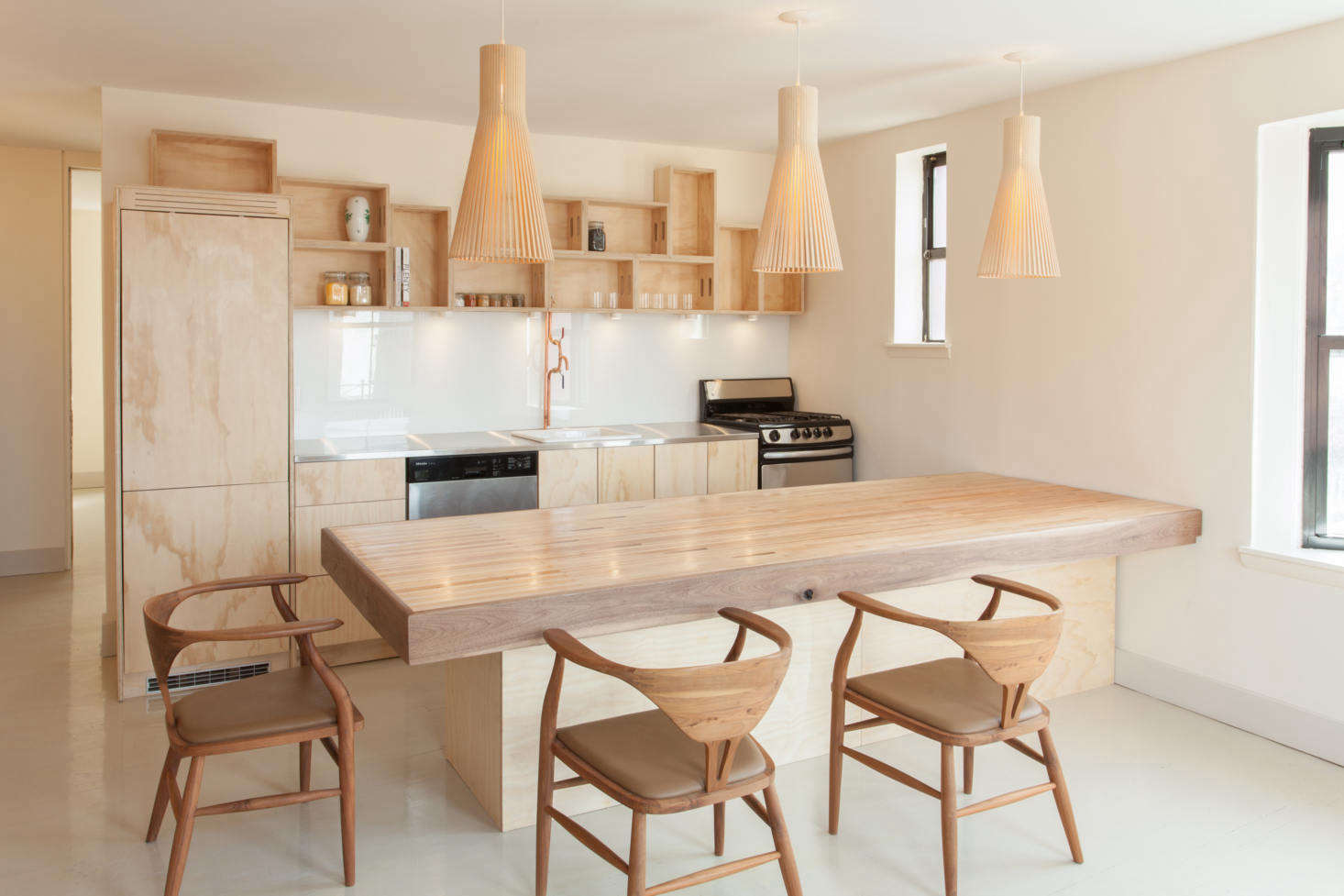 The architects began by opening up the space to the living room—the kitchen/dining half is now approximately 0 square feet and includes a peninsula that works as both a food-prep counter and table.