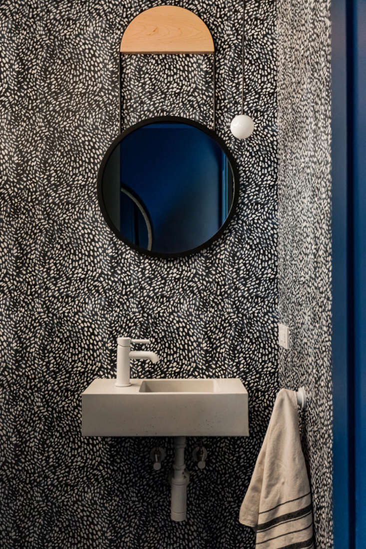 A petite powder room is papered in a design by Rebecca Atwood.