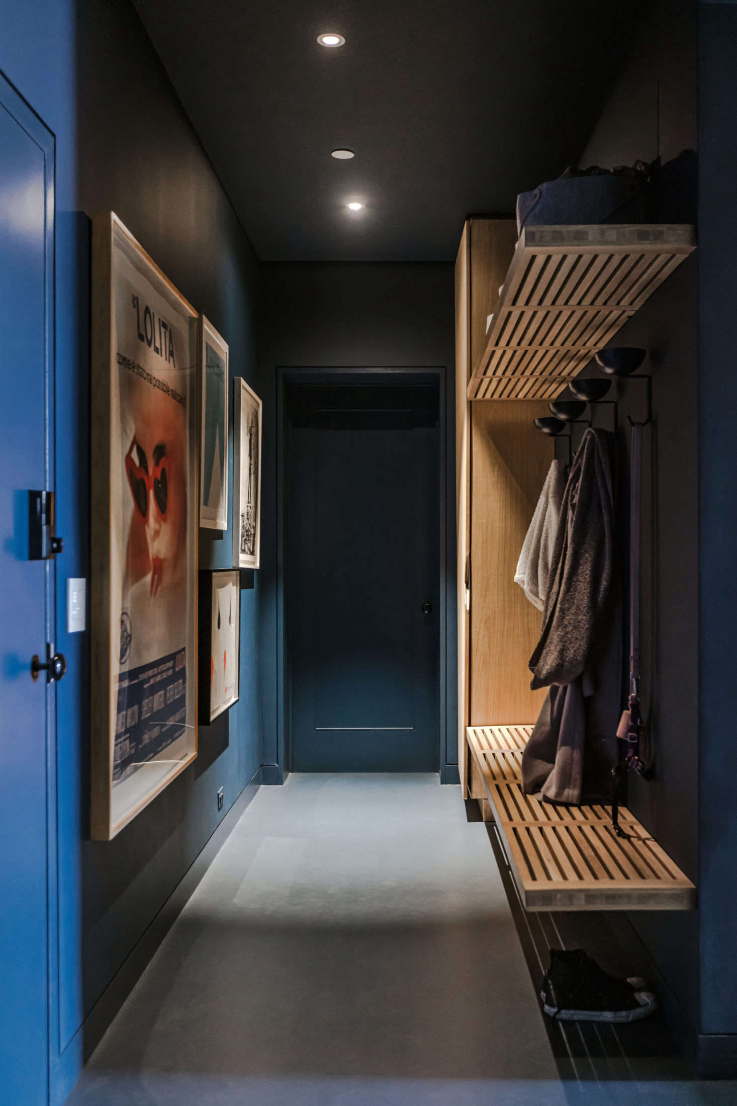 The deep layout of the combined apartments meant that some spaces were bathed in natural light while others were set far back from the banks of windows. The solution? Embracing the dark. The entryway is furthest from the windows, so it got a wash of blue paint on the walls and dark blue linoleum on the floor.