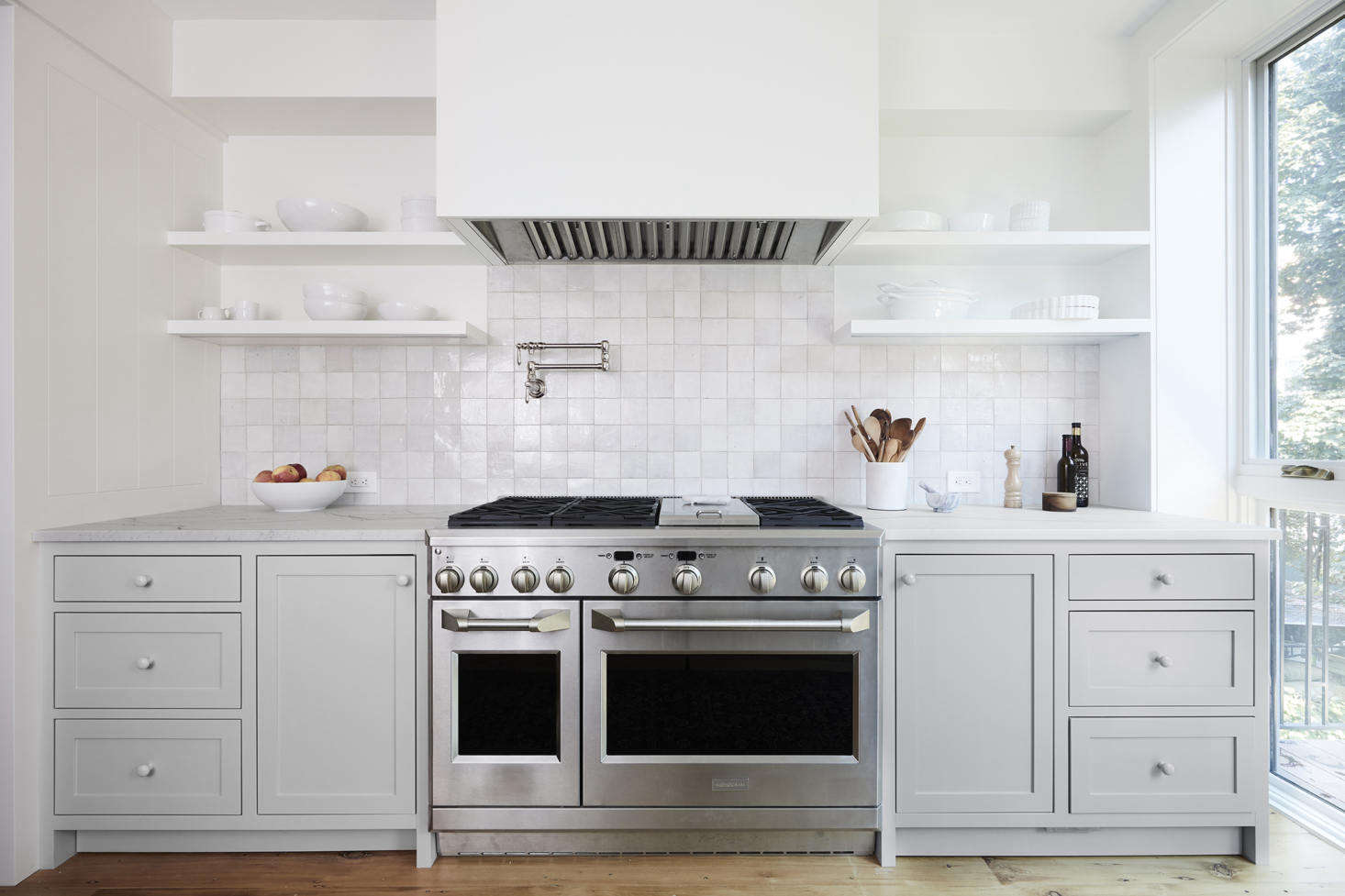 The owners purchased their 48-inch Wolf double-oven range second hand. It has a Viking hood set in a custom cover. The backsplash is in Weathered White Zellige from Clé Tiles. The pot filler above the stove came from Signature Hardware. Considering one of these yourself? See Domestic Dispatches: Why Your Kitchen Needs a Pot Filler Faucet.
