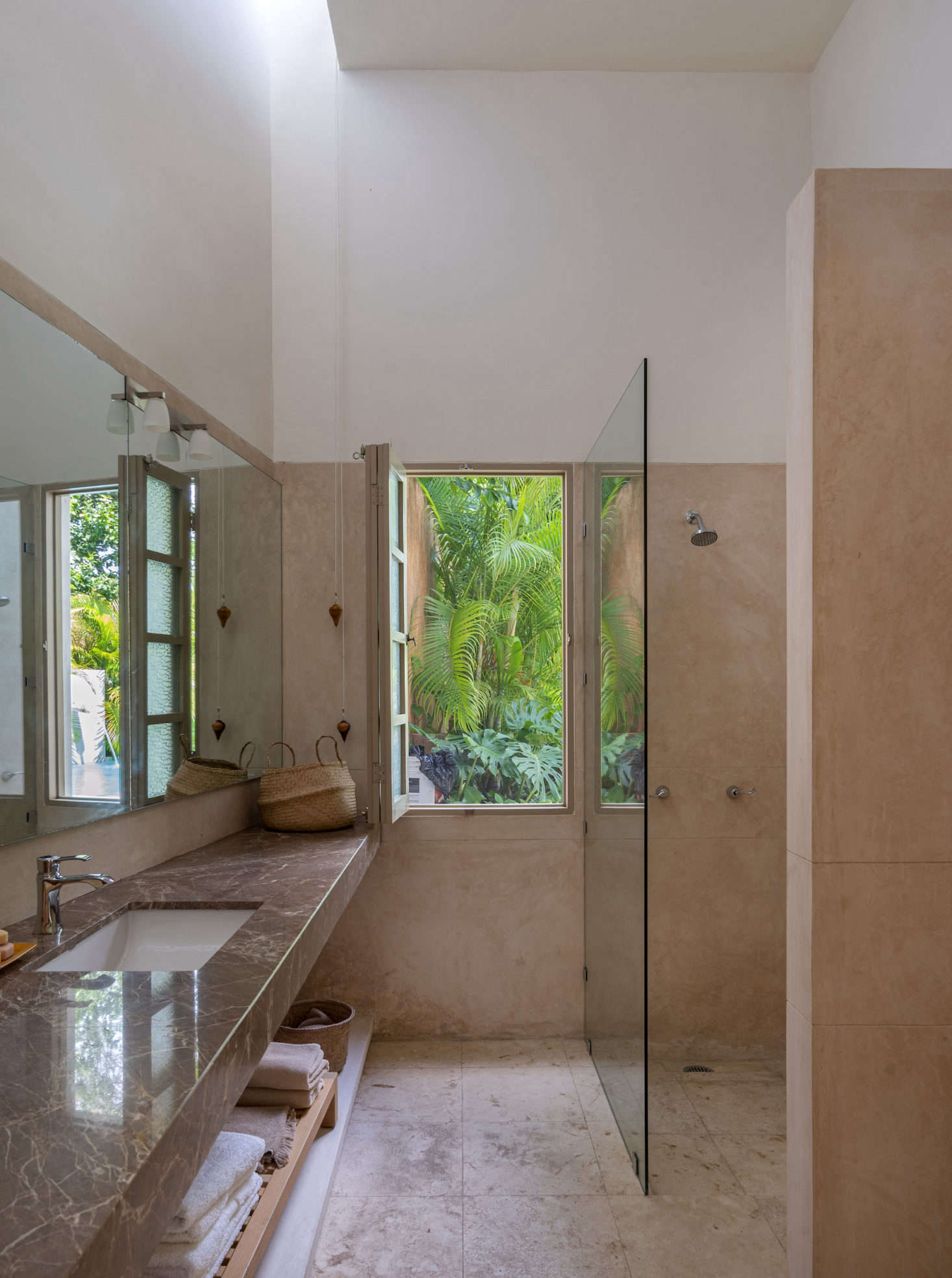 The en suite bathroom features a Brazilian marble counter and a shuttered window that looks out onto the pool.
