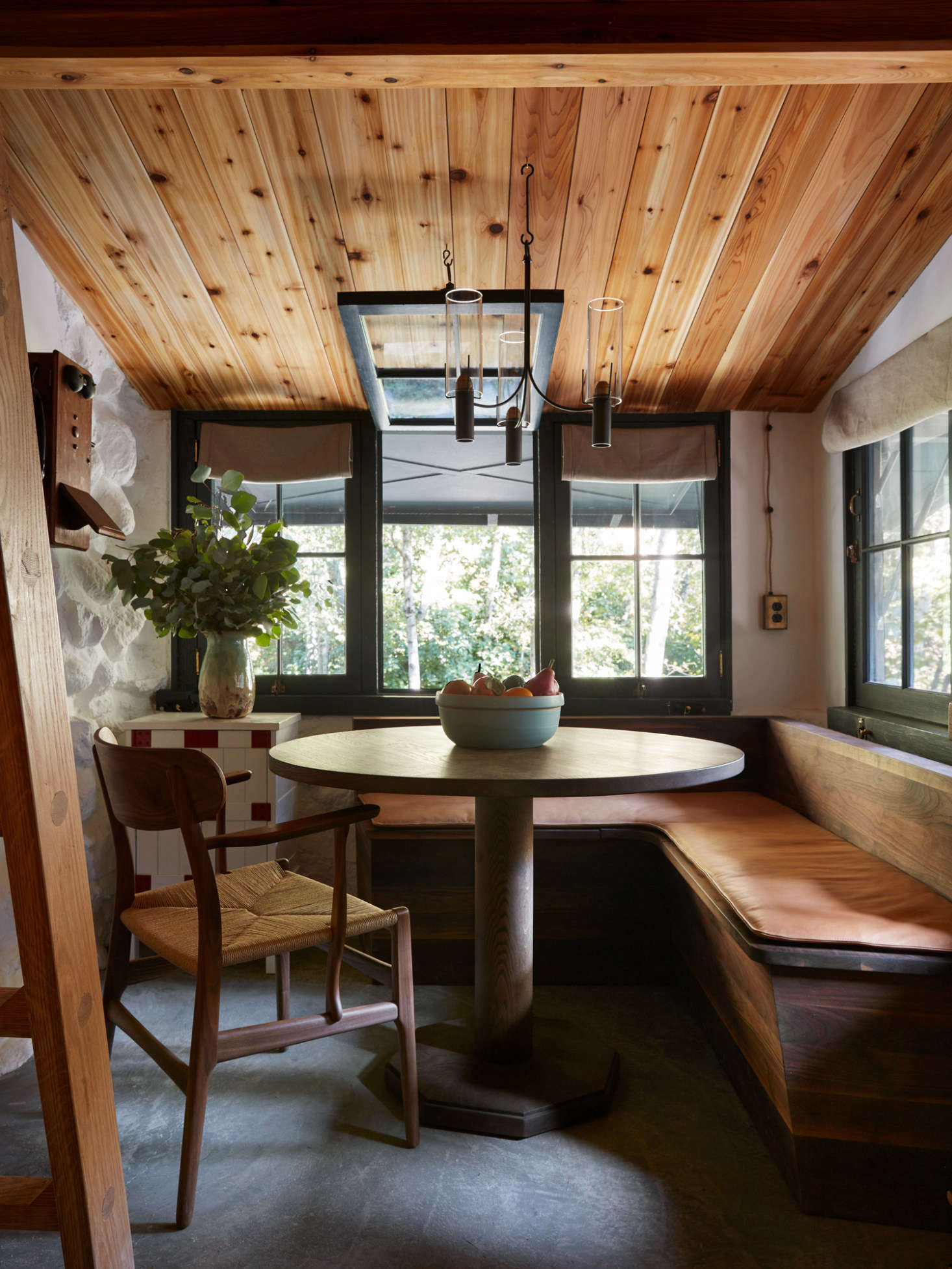 Concrete floors take over in in the kitchen. All the walls inside are limewashed. A ceiling light from Robert Long Lighting hovers over the dining nook.