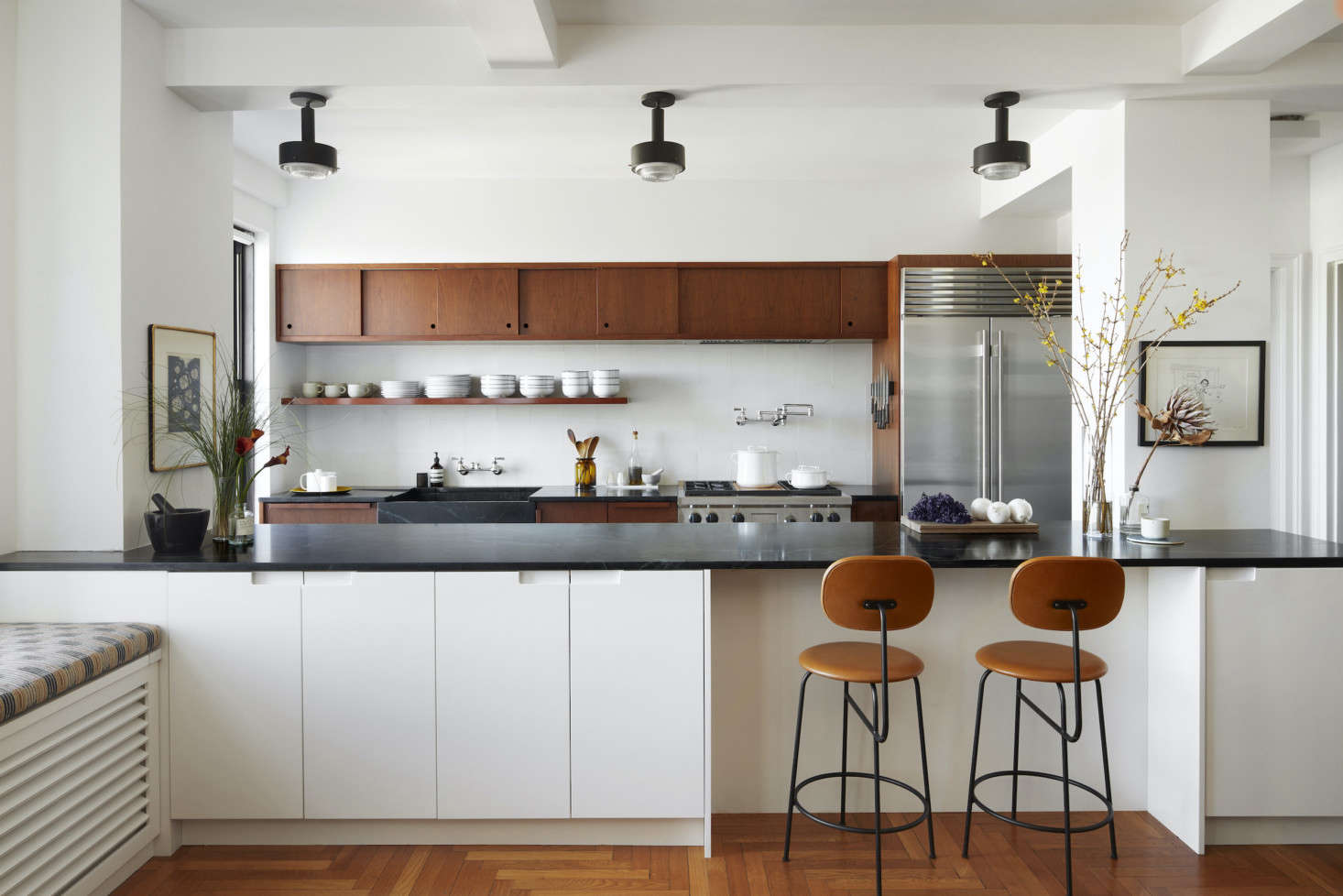 Tiny no more, the kitchen, inspired by California mid-century design, is now centralized and open to the dining room. The lighting fixtures here are 60s Scandinavian pendants by Arnold Wiigs Fabrikker from src=