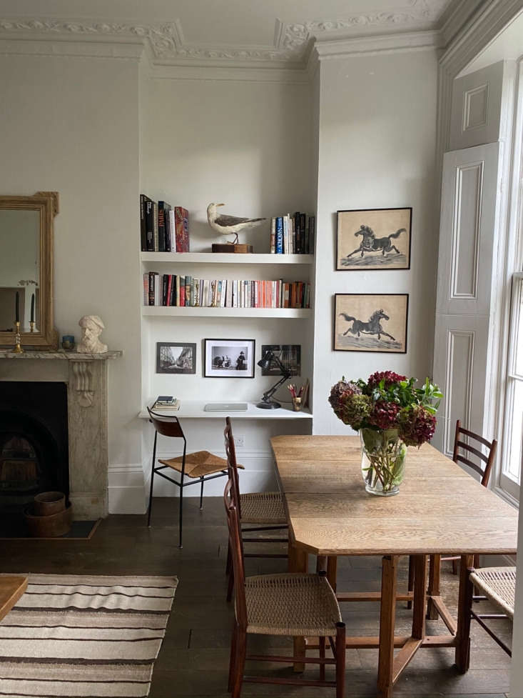 The living room triples as an office and dining room. The dining table is an eBay score; the chairs are from vintage store Sauce. The pair of horse paintings are among her favorite finds; she bought them in a charity shop in Pimlico for just £4.