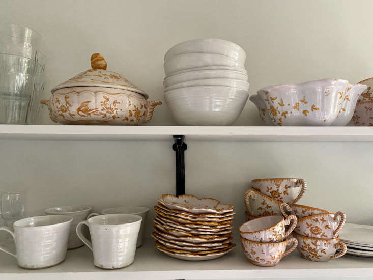 Her collection of gold and pink Moustiers faience earthenware, found at an auction, sit on open shelves.