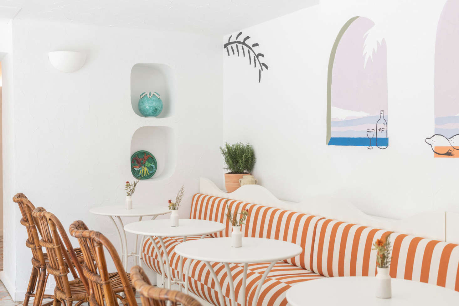 French artist Franck Lebraly painted a whimsical mural above the striped banquette in the cafe.