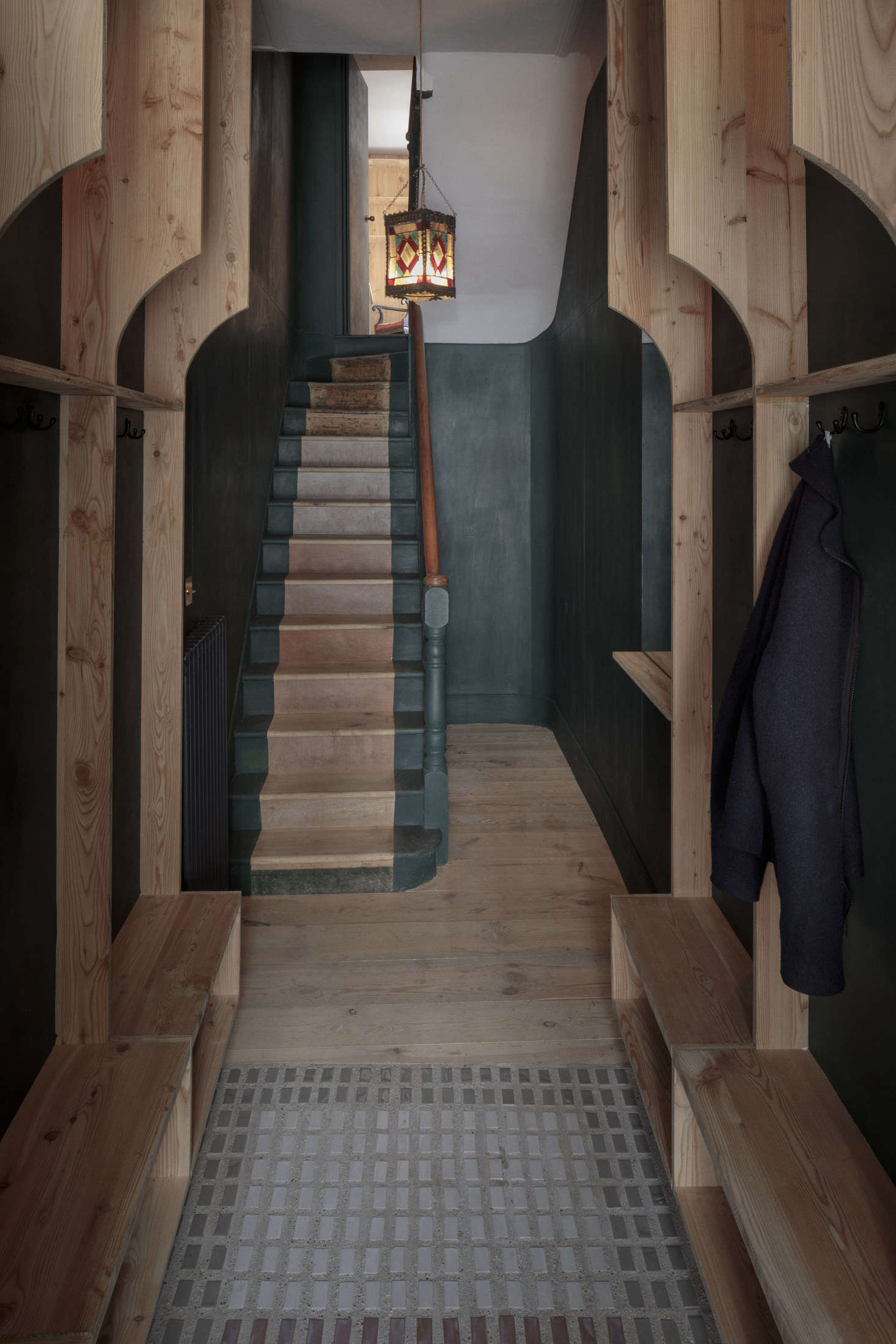 The entrance hall on the ground floor has its own two-toned stair in the same dark green (that&#8