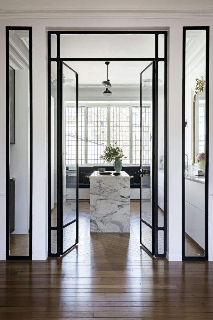 Revolving around a center island, the kitchen incorporates walnut, marble, and metal into the design. Tall glass doors open up to the space.