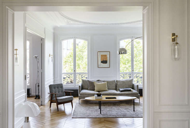Filled with neutral tones, the living room draws the eye to the oversized arched windows that let natural light fill the space.