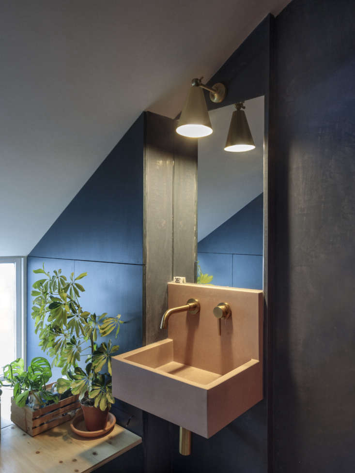 The en suite wash area has blue tadelakt walls and a pink concrete basin, the Kern by Kast.