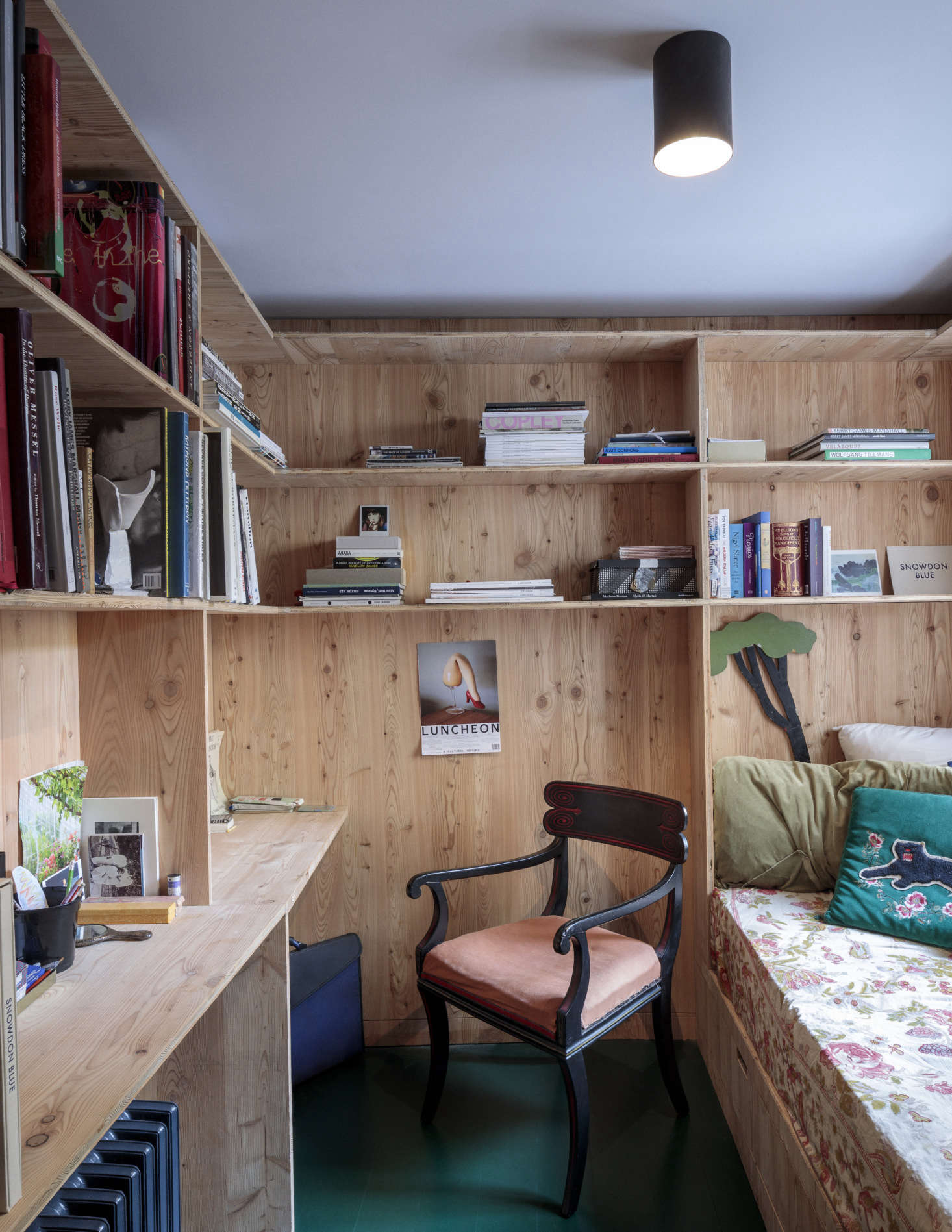 Designed to feel like a retreat, the combination study and guest room has a built-in daybed, desk, and shelving of larch. The old floorboards are painted a glossy deep green.