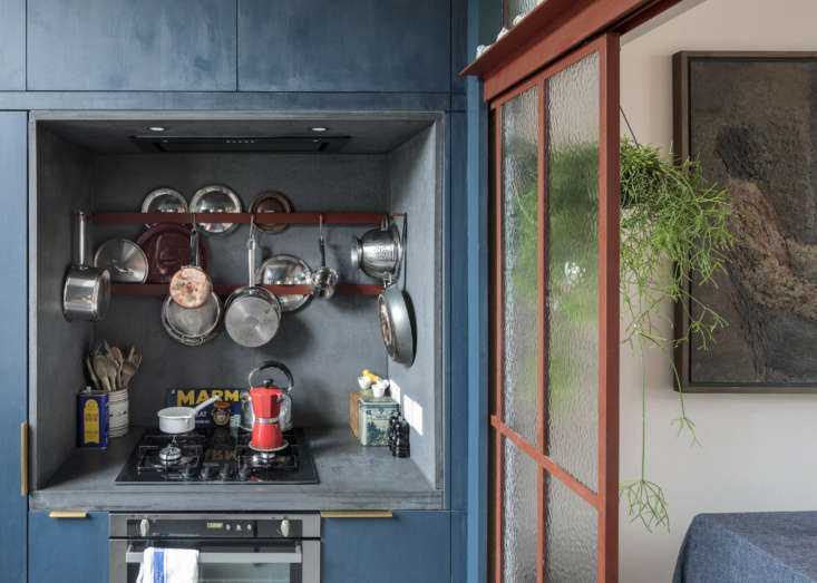 The compact cooking niche has a concrete surround made by Kast. The custom cabinets are blue-stained spruce: &#8