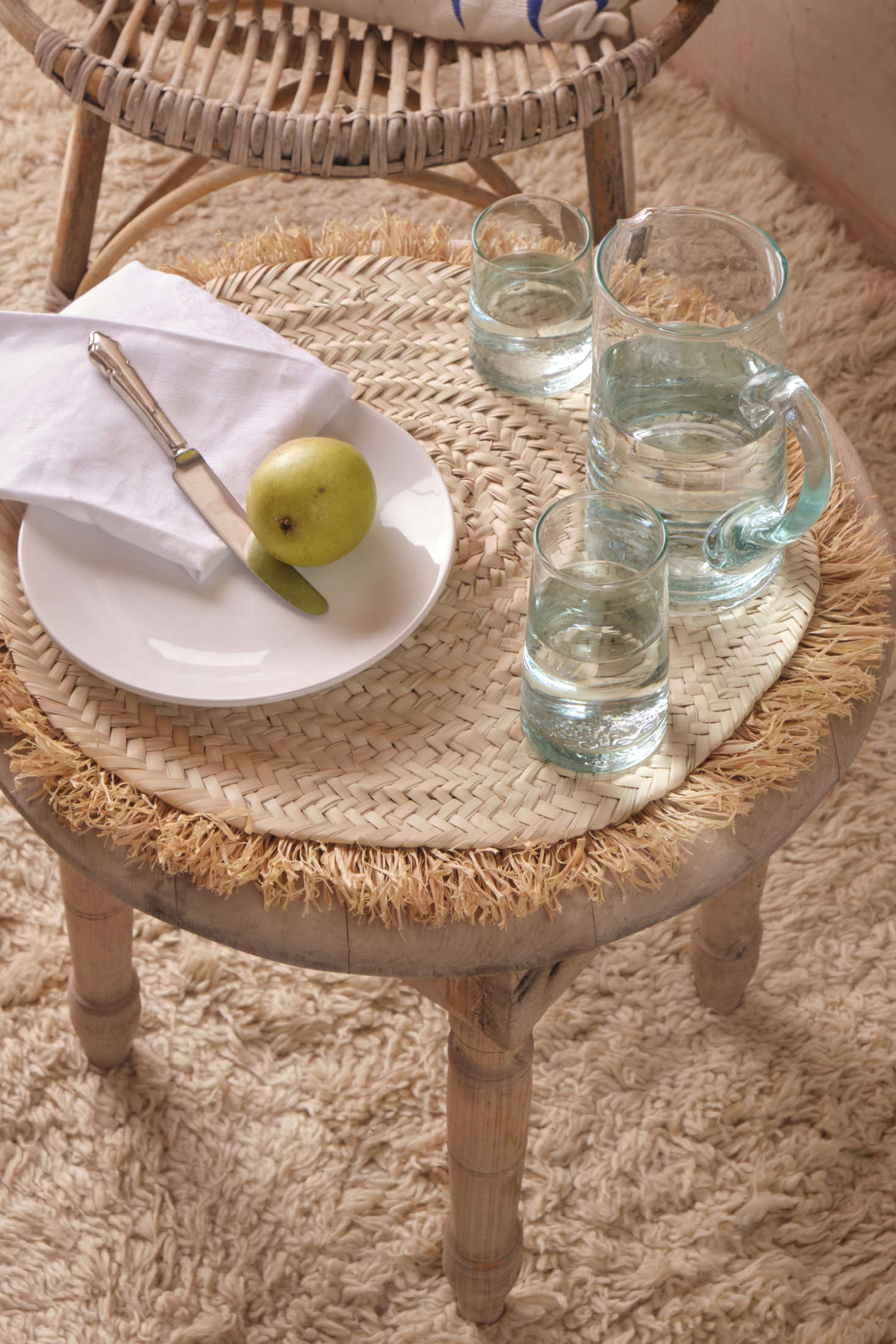 A selection of Revival's new globally made tablewares: the Handwoven Palm Placemat ($59), handwoven in Morocco from sun-dried palm leaf with a jaunty raffia fringe, and a recycled glass Moroccan Pitcher ($39) with a sturdy handle for easy pouring. Below is a one-of-a-kind vintage Moroccan hand-knotted rug; for similar finds, head here.