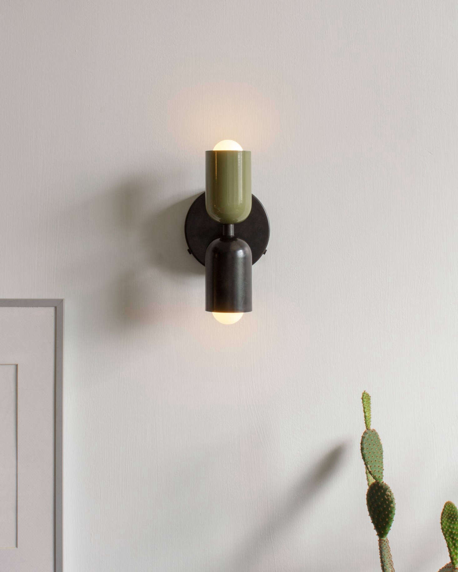 The Up Down Sconce with a Reed Green top shade and Black bottom shade. The light is 4 7/8 in wide by 9 5/8 in tall and is available hardwired or with a plug-in cord.