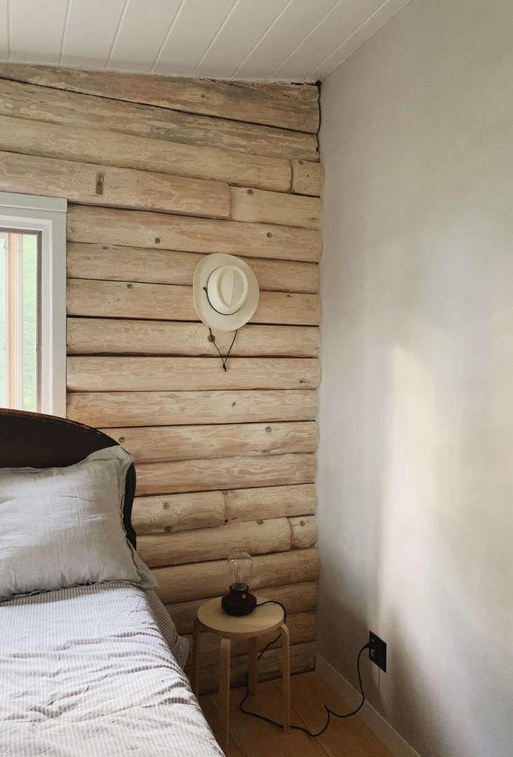 aquiet, textural bedroom corner where logs meet limewash. 15