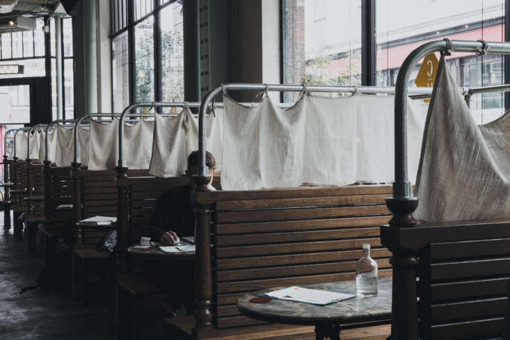 A stretch of wood-clad banquettes are fitted with simple cloth curtains.