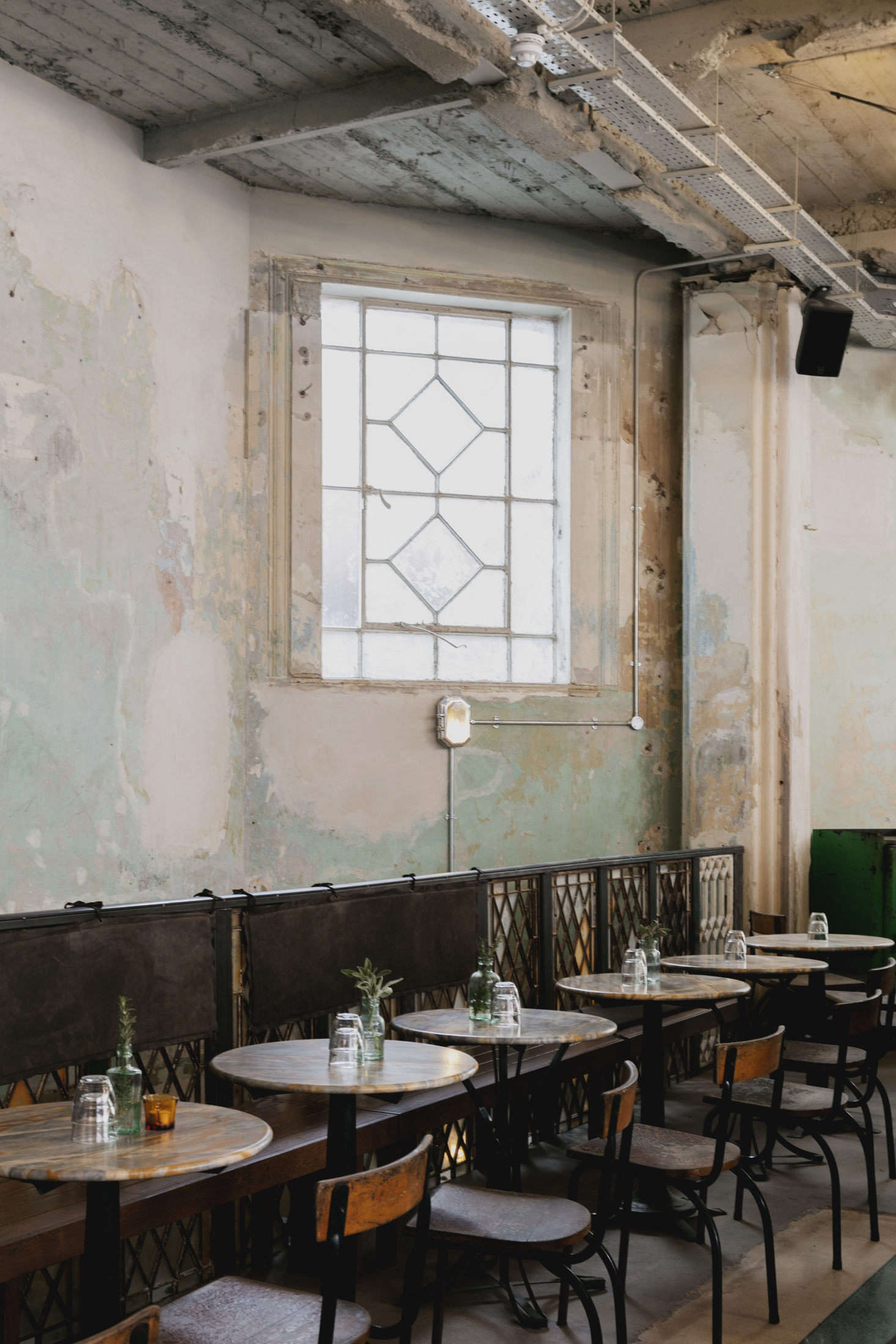 The walls were left stripped and patinated, to charming effect. Not shown is the open kitchen, designed with market stalls in mind and raised so that diners can see in. Photo by Mariell Lind Hansen, courtesy of Red Deer.