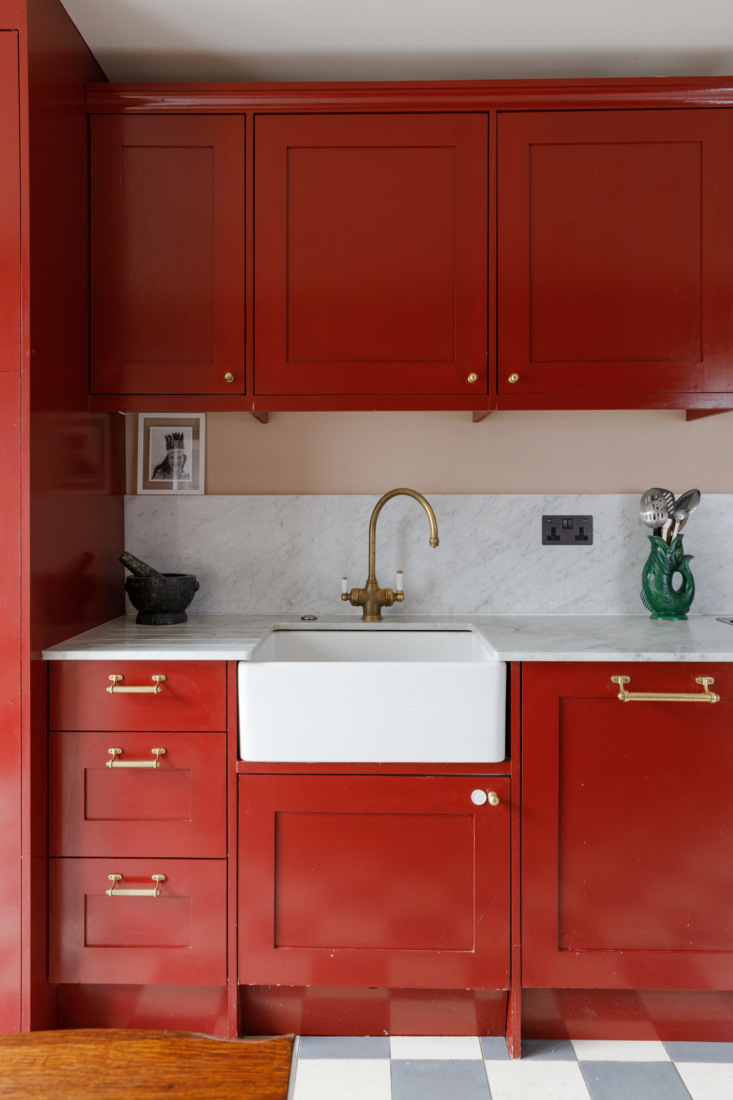 A marble countertop with integrated drainboard removes the need for a clunky dish rack in a small space. The brass knobs and pulls are from Balineum.