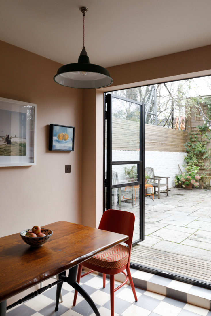 The south-facing room is small but a pair of Crittall steel doors leading to the patio helps bring in light. The gray and white checkered Terrazzo-tiled floors are perhaps Adam&#8