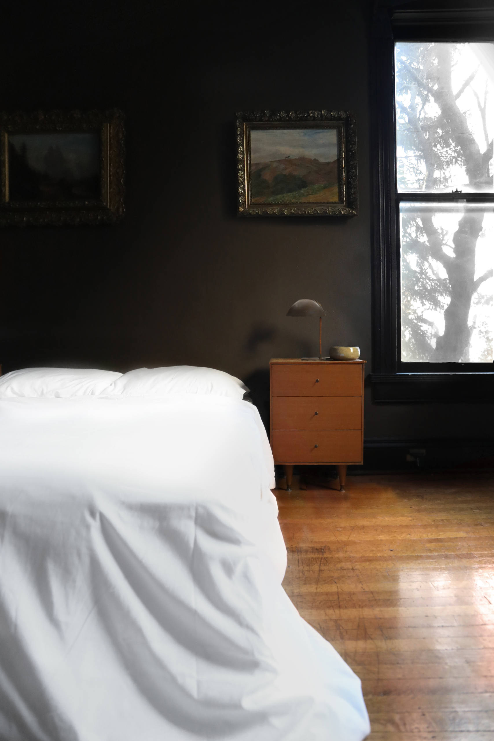 Pillowy white bedding contrasts with the moody walls.