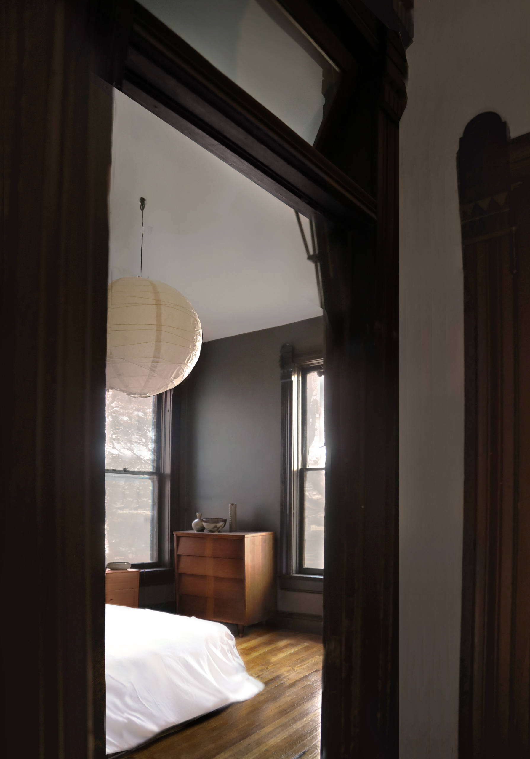 In a bedroom, another paper lantern accentuates the high ceilings.