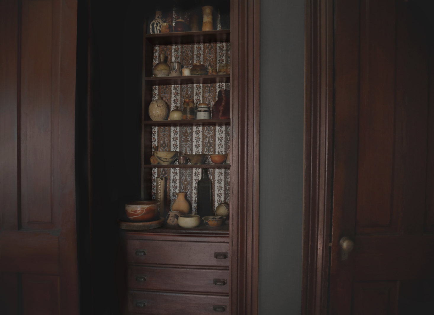 An original built-in cabinet with papered back holds ceramics.
