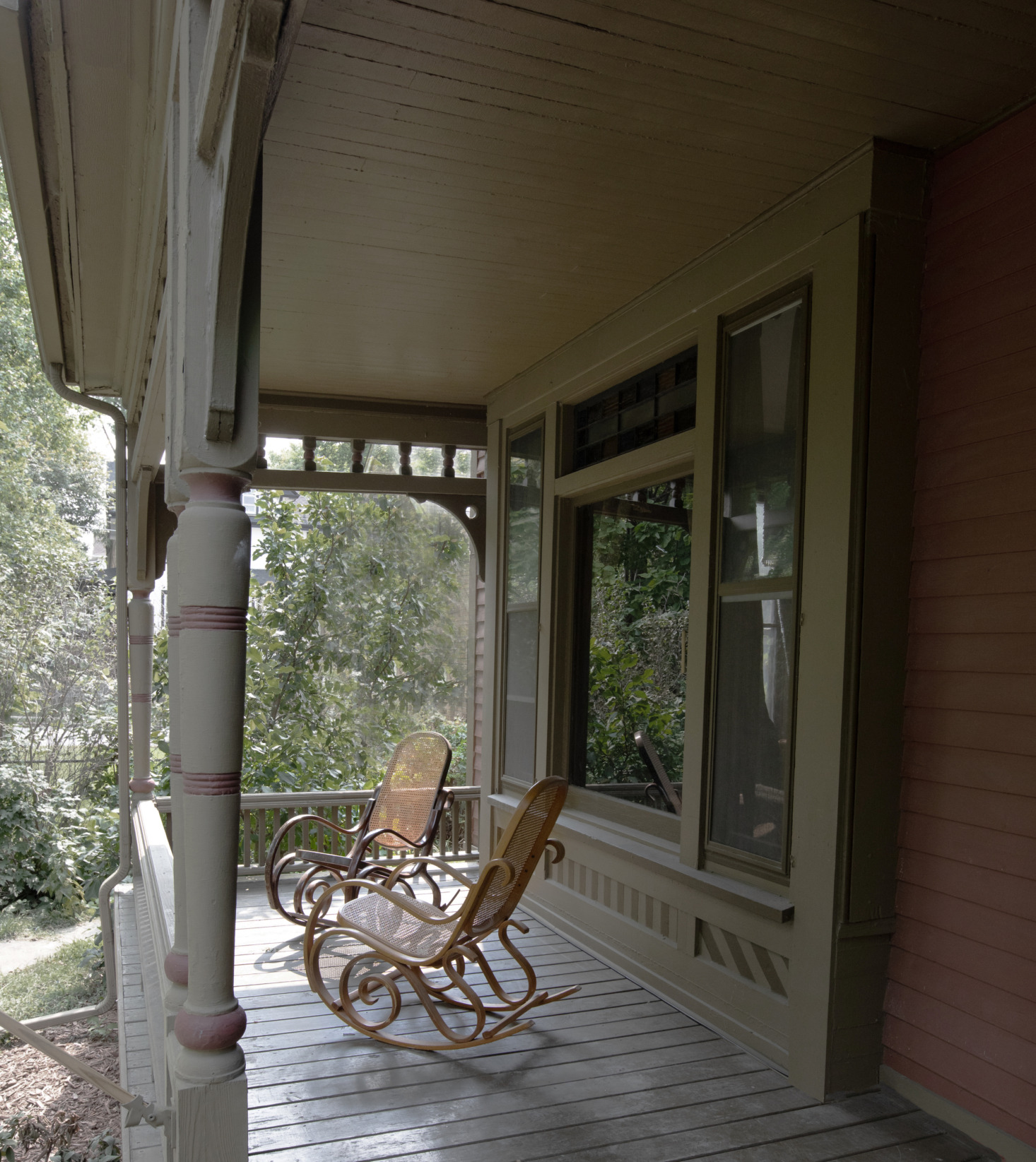 Two old-world rocking chairs on the porch. And the moody palette continues outside: The exterior is painted in Meadow Trail and Moss Rose, both by Sherwin Williams.