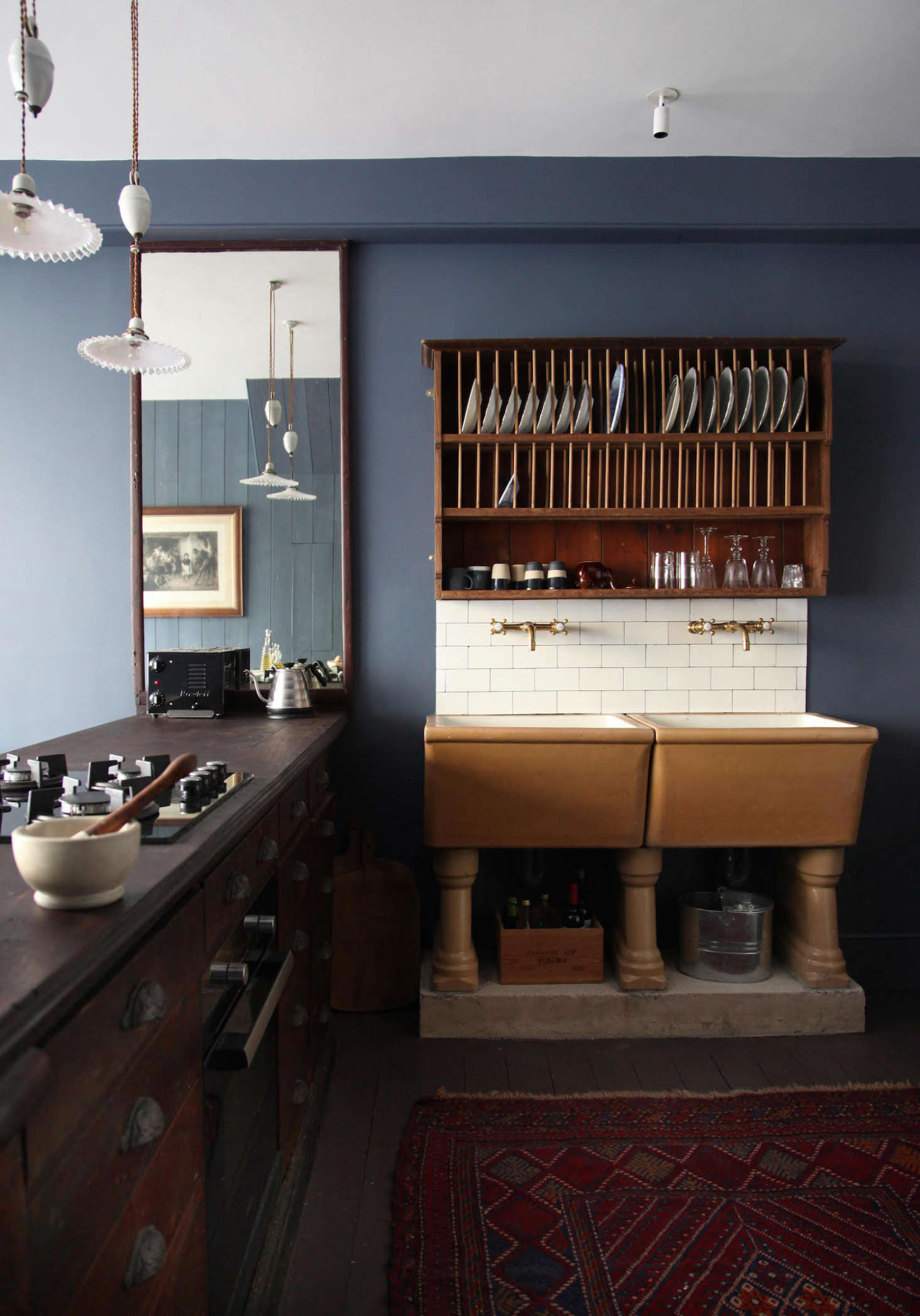 """The project required a lot of sleuthing and reimagining. """"In a back room we found what we imagine was the original counter, and decided to use this to house the kitchen, reinstating it in the same position per the 90 plans,"""" says Patrick. Made of mahogany, it's now fitted with a cooktop and stove, and immediately to their left, an under-counter fridge hidden behind what looks like a set of drawers. The mirror was found in the space and """"happened to fit perfectly."""""""