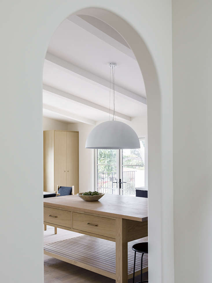 Another archway frames a view of the kitchen/dining area. The oversized white pendant is from Dainolite, the counter stools from Menu.