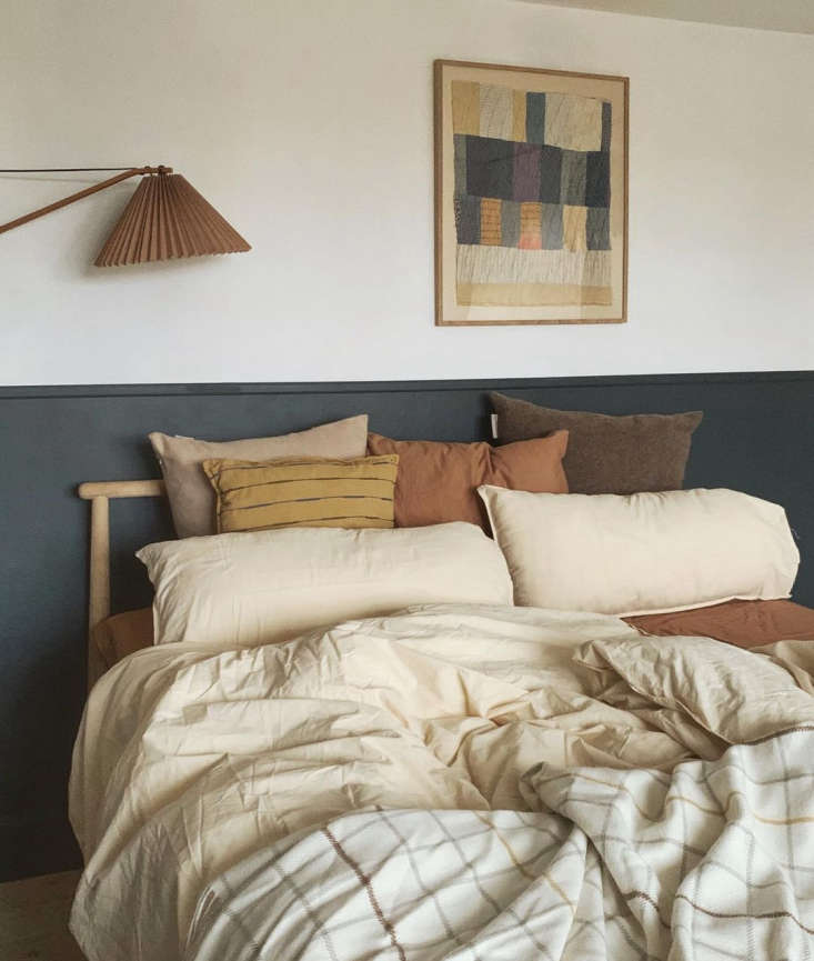 The main bedroom on the second floor, with bedding and pillows from Silkeborg Uldspinderi and Sweden-based Midnatt. Johanne found the framed quilt above the bed via Piece by Piece by Piece, which specializes in vintage American quilts, framed.