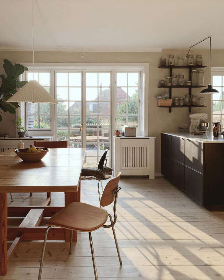 The combined kitchen and dining room at the back of the house, with original s wood floors and doors out to the back garden. It&#8