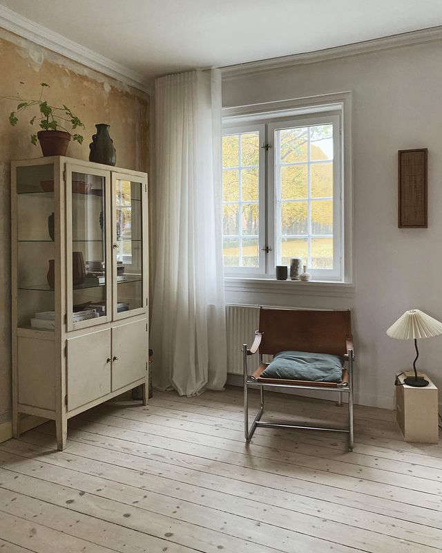 In the living room, a Mobring chair and a glass cabinet for displaying collected ceramics. The couple stripped a pale-yellow wall to reveal the pared-back plaster, at left.