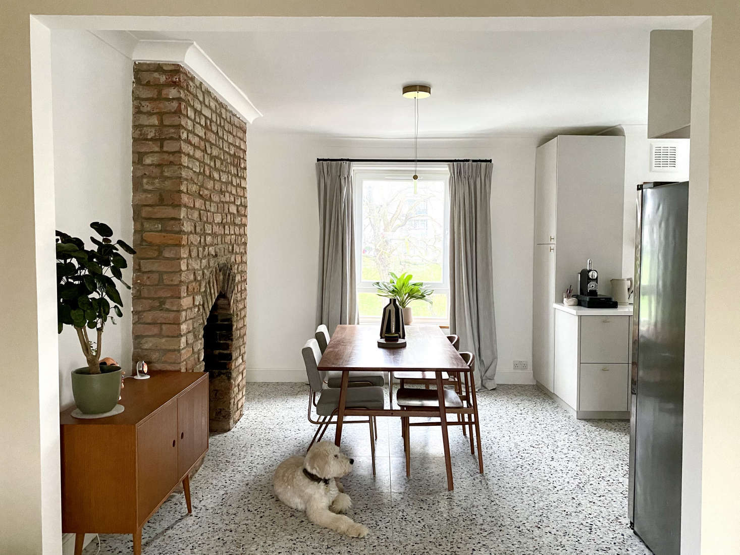 The kitchen opens to the dining area with a newly revealed brick fireplace formerly fronted by a reproduction cast-iron—&#8