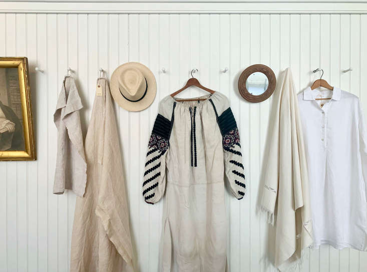 A 30s Ukrainian dress and a linen nightshirt by Area hang on pegs lining the back wall. The shop&#8