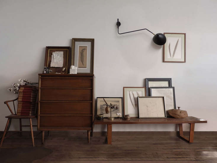 A vintage Serge Mouille light hangs above a collection of framed artwork, casually propped against the wall on a Nelson-style bench. The dresser is a hand-me-down from Jeff&#8