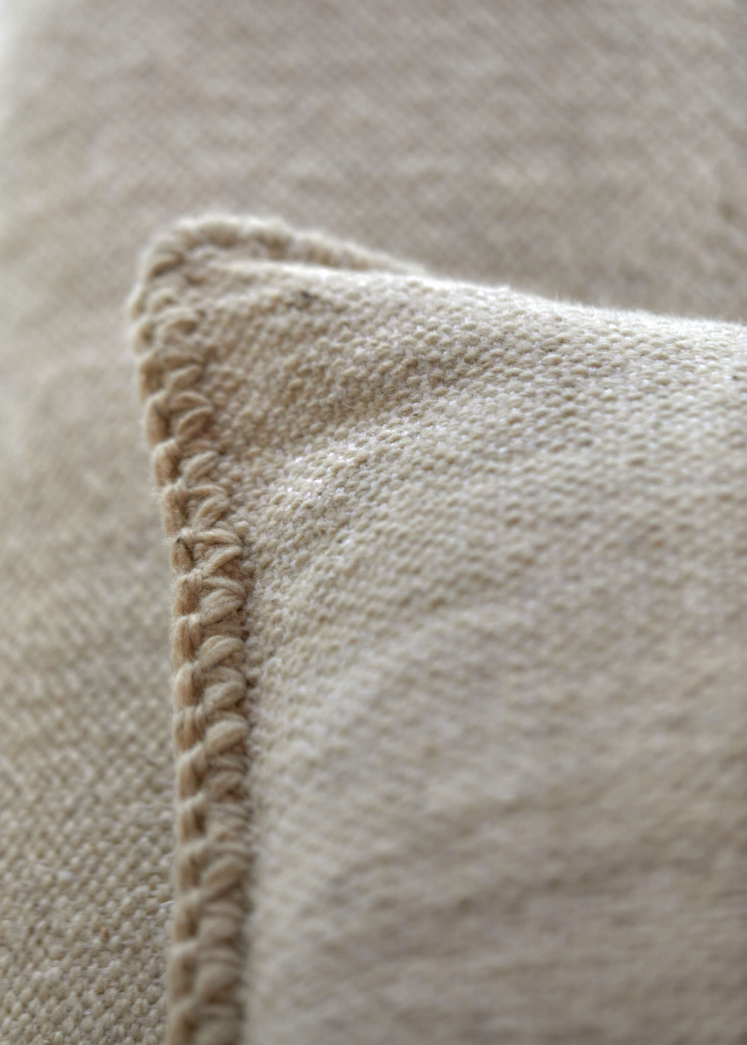 The bedding is made of textiles hand-stitched by local Oaxacan artisans using natural, neutral-toned fibers.