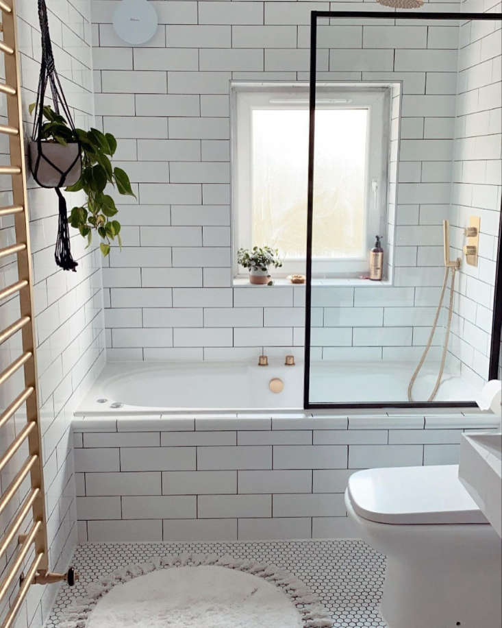 Bathroom of the Week Ferren Gipson Upgrades Her London Loo and Makes Room for the Laundry &#8\2\20;We were going for Victorian public bath meets a modern boutique hotel,&#8\2\2\1; says Ferren. Subway tiles with black grout now pattern the walls and run up the side of the existing tub, newly fitted with a shower (the Arezzo Brushed Brass Showerhead and Bath Knobs are from Victorian Plumbing). Ferren considered black fixtures but liked the warmth of brass. The matte white Hexagonal Mosaic Tilesare from Topps Tiles.