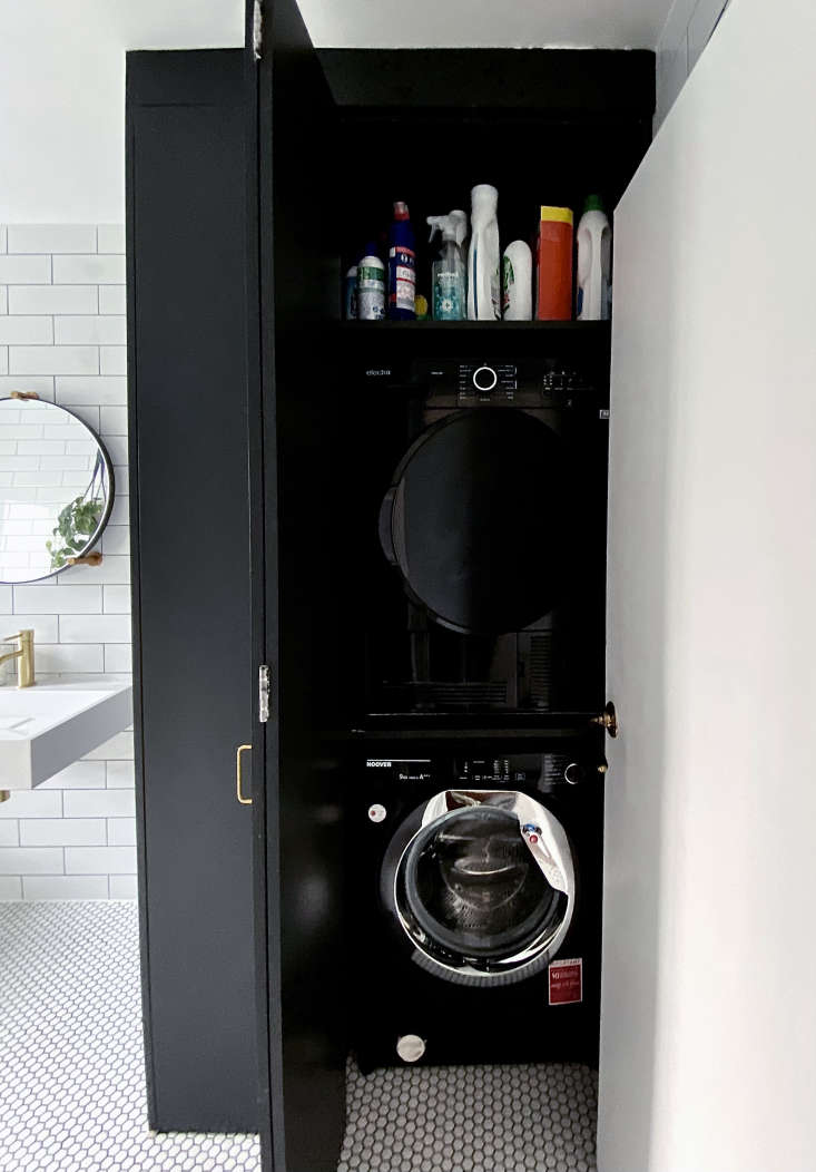 To squeeze in a stacked Hoover washing machine and Electra dryer, Ferren had her crew replace the existing shower stall with a painted wood cabinet. The hinged door enables it to work in the space, and there&#8