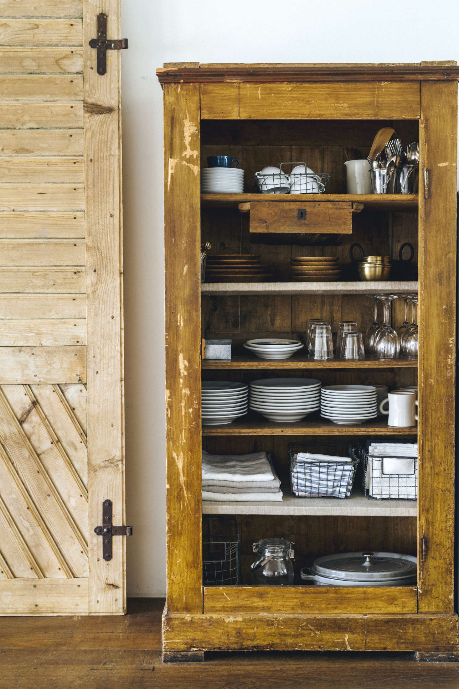 A vintage cabinet holds kitchen essentials; linens are stored in Yumiko&#8