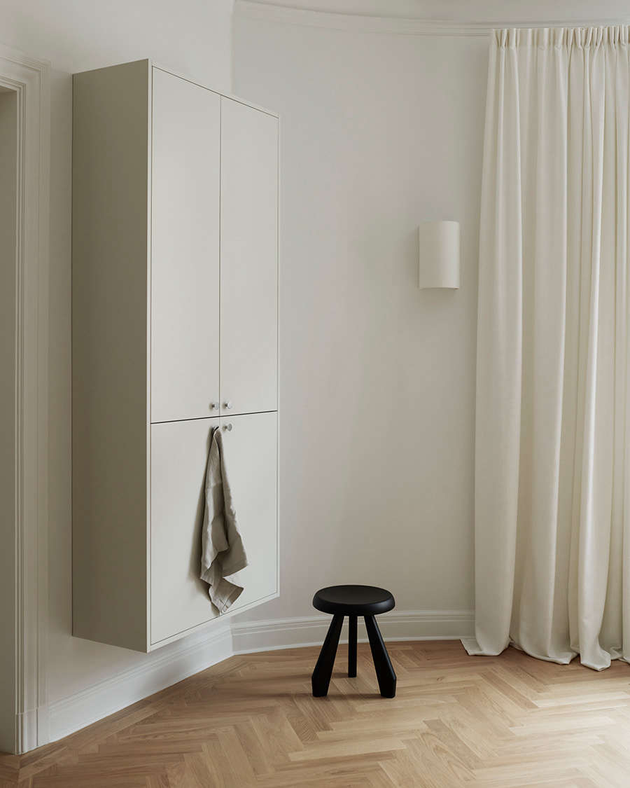 A Tabouret Meribel stool by Charlotte Perriand sits next to a floating wall unit.