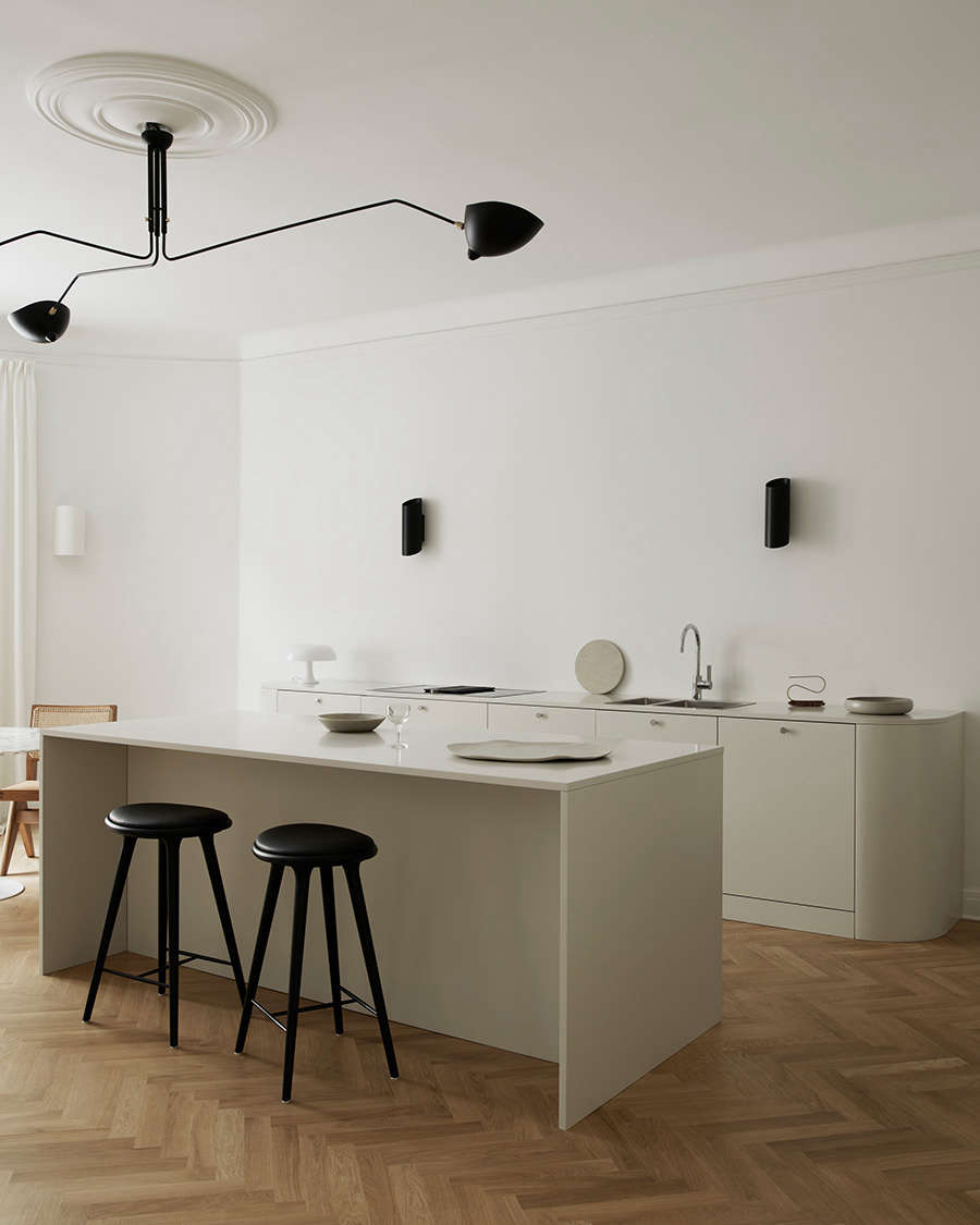 Black accents—a Serge Mouille ceiling light, wall lights by Serax, and stools by Mater—punctuate the otherwise pale room.