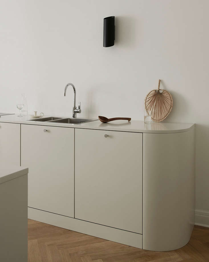 The rounded lower cabinets and countertop, more akin to a sideboard than kitchen built-in, reference a curvy sofa in the living room. The faucet is by Dornbracht.