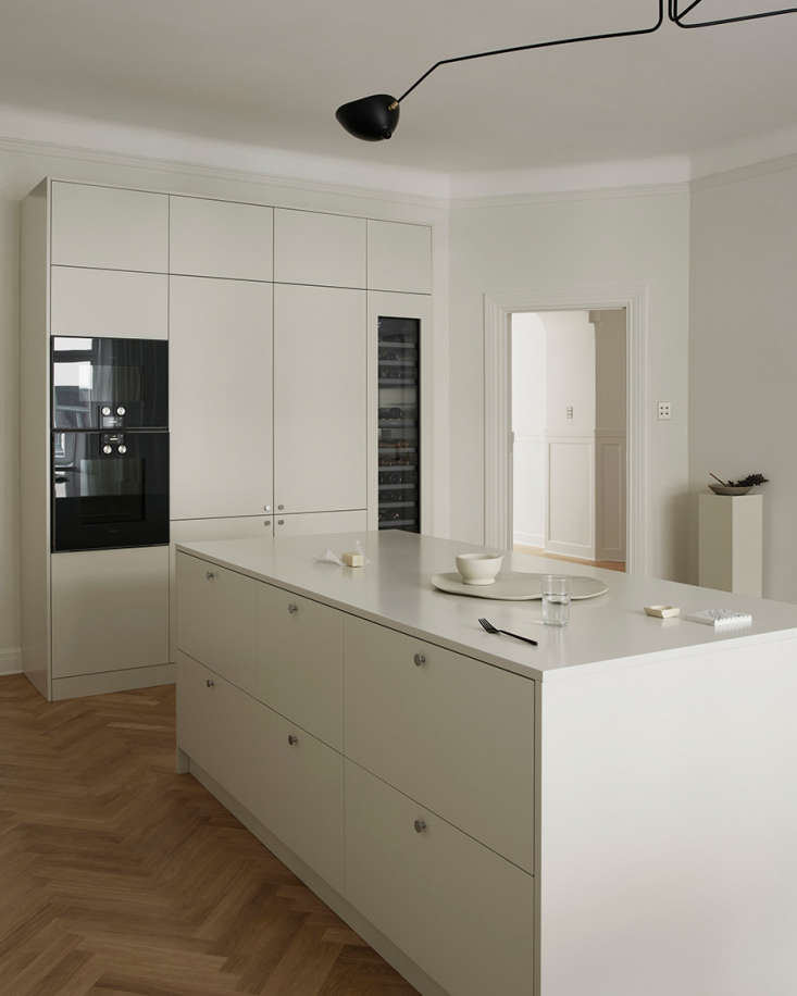 Hidden from the living room view is a wall unit that conceals the refrigerator and freezer.