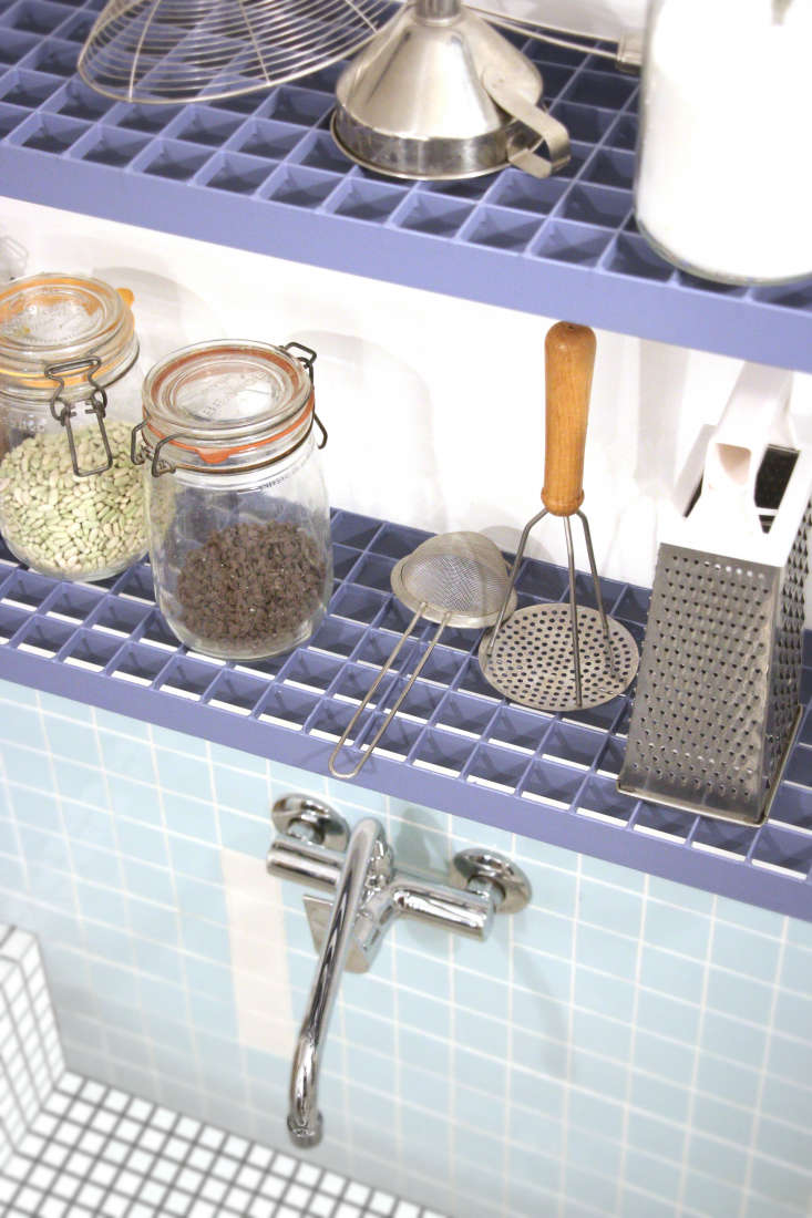 The steel grating works well for drying kitchen tools. It was given a blue powder-coating to match the steel pulls and edging.